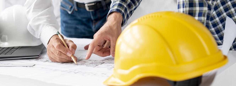 Architekten besprechen eine Bauzeichnung mit Bauhelm auf dem Tisch