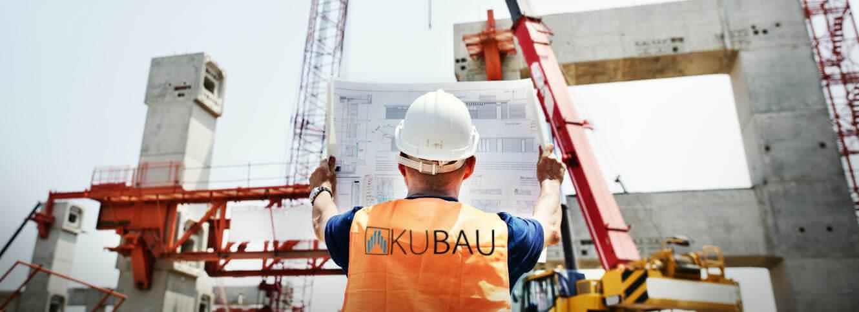 Bauleiter des Bauunternehmens Kubau GmbH begutachtet Baupläne auf der Baustelle