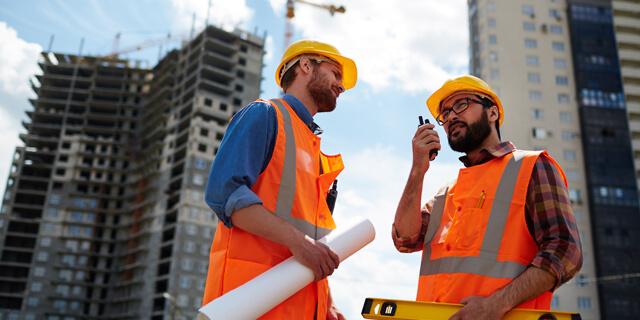 Zwei Baustellen Mitarbeiter in Warnwesten und Bauhelmen sprechen über Funk mit dem Bauleiter auf einer Baustelle