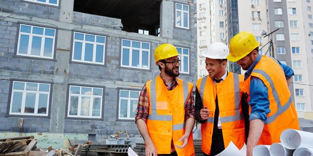 Drei Bauarbeiter vor einer Hochhaus Baustelle in oragen Warnwesten zusammen mit dem Baulleiter mit einem weißen Bauhelm