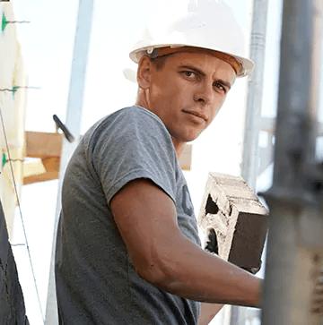 Bauunternehmenmitarbeiter als Maurer während der Arbeit an einer Mauer.