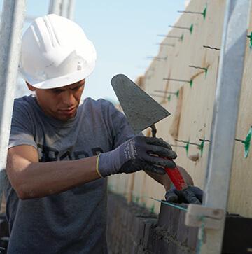 Maurer-Bauarbeiter mit Helm passt die Ziegelsteine passgenau an die Maurerdichtungen an.