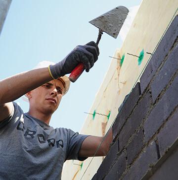 Maurerbauarbeiter bearbeitet auf einer Baustelle eine Mauer.