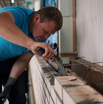 Maurermeister mit Zement auf Ziegelsteinen mauert eine Mauer.