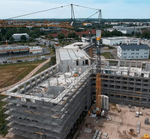 Große Baustelle auf Drohnenaufnahmen von dem Bauunternehmen mit Kran. Das Gebäude hat eine moderne Archetiktur und Grundform