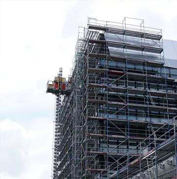 Trockenbauwände werden mit einem Baukran auf das Dach eine Baugebäudes befördert