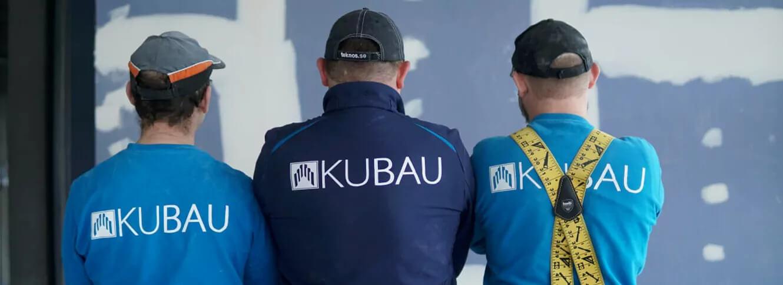 Drei Trockenbaumonteure sitzen mit dem Rücken vor einer Trockenbauwand mit dem Firmenschriftzug KUBAU