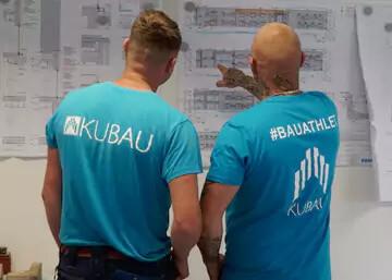 Zwei Bauleiter mit Kubau Firmen Tshirt vor einem Baustellenplan an einer Trockenbauwand